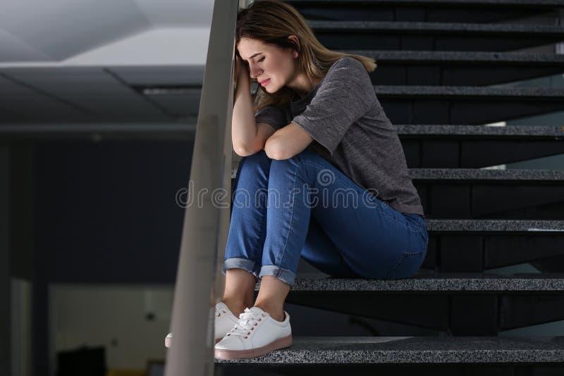 孤独的沮丧的妇女坐台阶 免版税库存照片