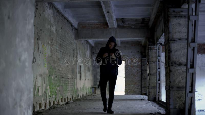 孤独的男孩走在被放弃的大厦的,美国黑人没有朋友,种族主义 免版税库存照片