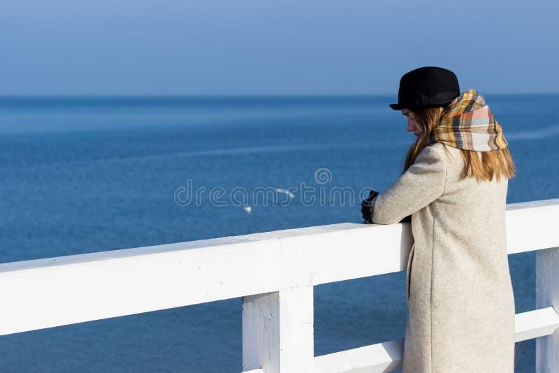 孤独的美丽的哀伤的女孩在码头站立在一个晴朗的温暖的秋天晚上在海 免版税库存照片