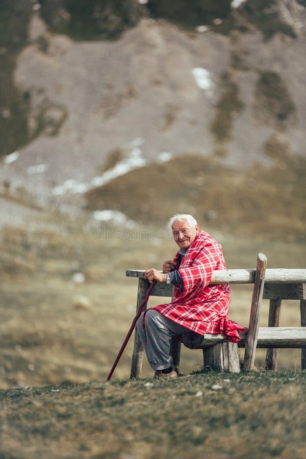 孤独的老人坐被吸收入他的想法的长凳 免版税库存图片