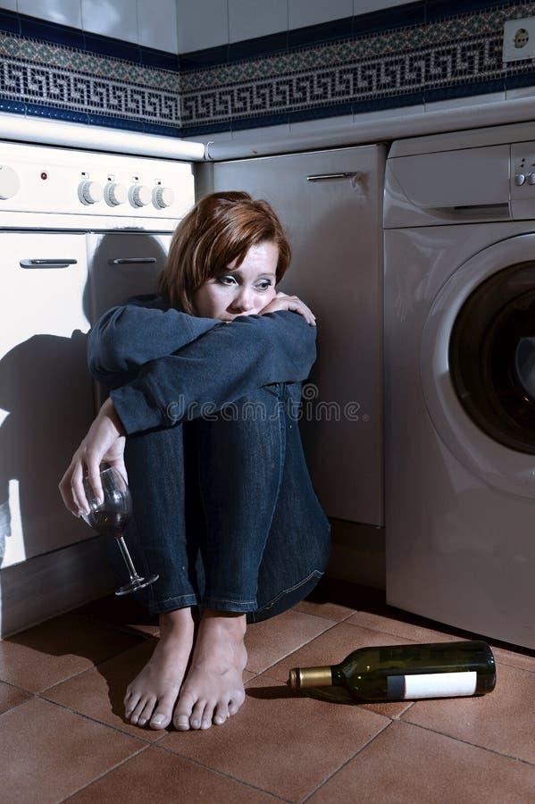 孤独的被喝的醺酒的妇女坐在消沉饮用的酒的厨房地板 库存图片