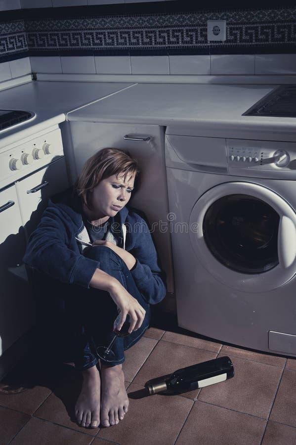 孤独的被喝的醺酒的妇女坐在消沉饮用的酒的厨房地板 免版税库存照片