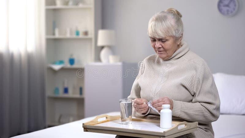 孤独的资深妇女在医疗中心,医疗保健的采取药片在晚年 免版税库存图片