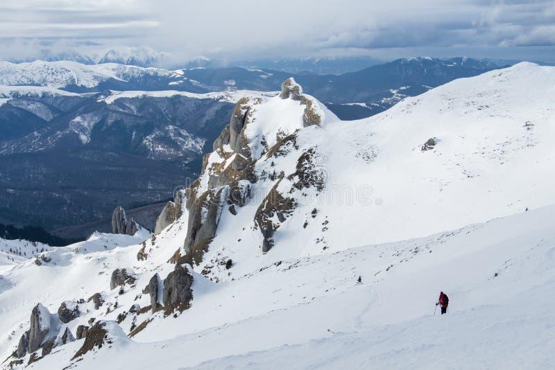 孤独的远足者下降的多雪的山坡 免版税库存图片