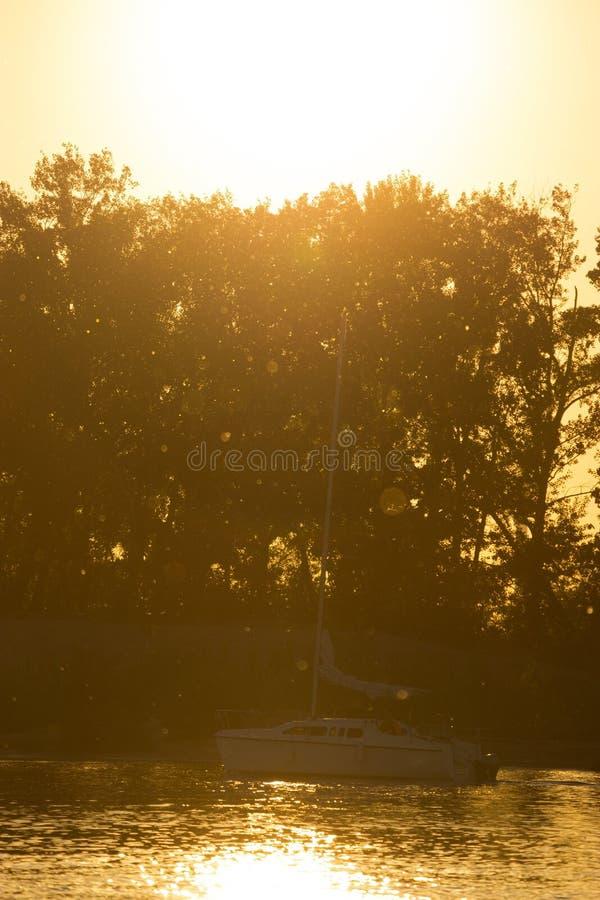 孤立小船航行到日落里 免版税库存图片