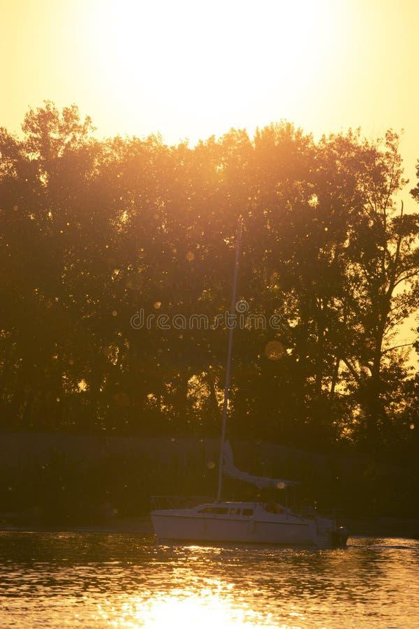 孤立小船航行到日落里 图库摄影
