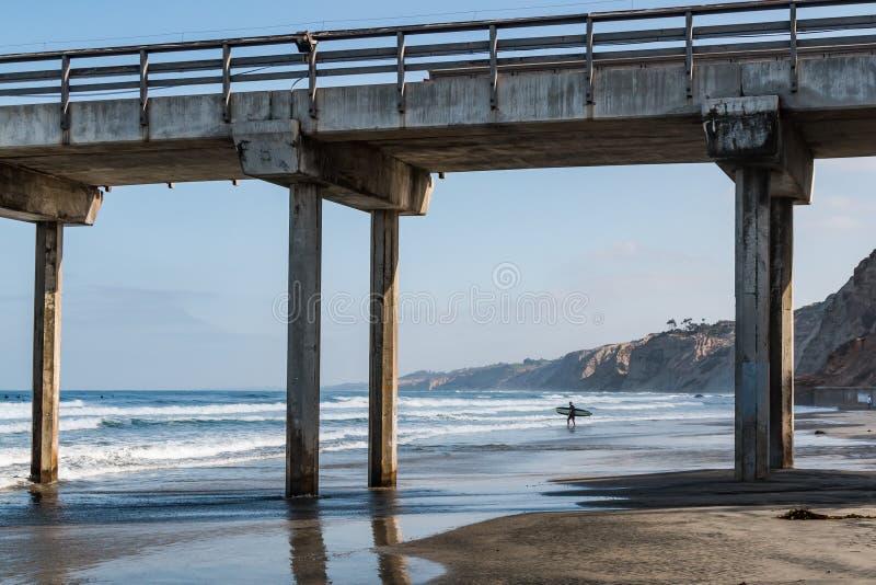孤立男性冲浪者在具体码头附近运载冲浪板 免版税库存照片