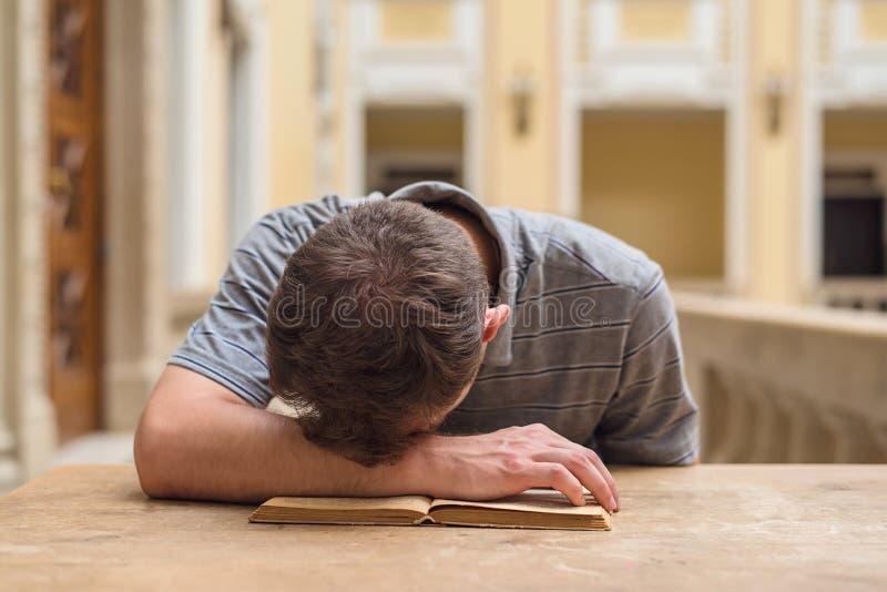 学习一个乏味主题的年轻学生人 免版税库存图片