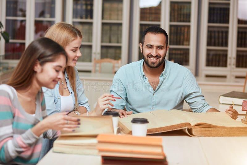 学习与书的小组多种族人民在大学图书馆里 免版税库存照片