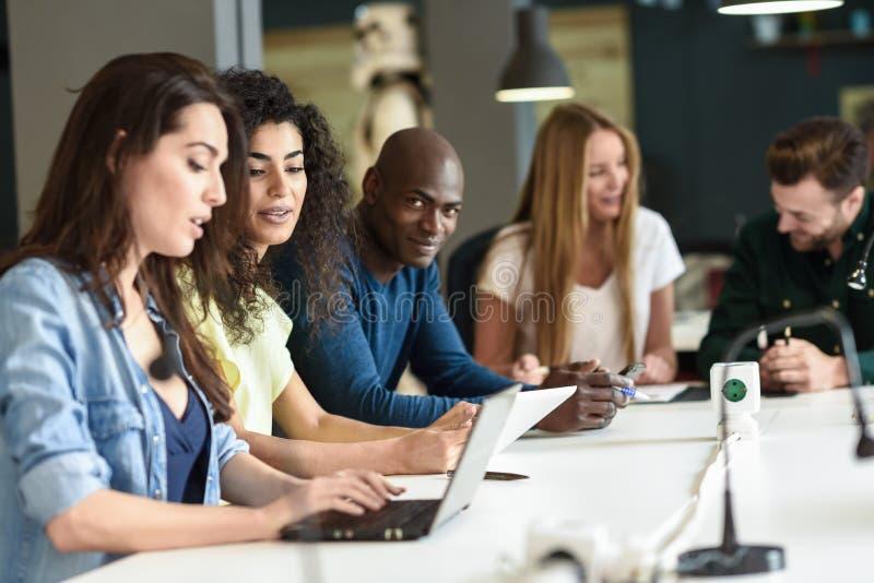 学习与便携式计算机的不同种族的小组青年人 库存图片