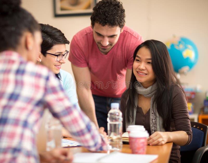 学习与同事的亚裔学生在教室 库存图片