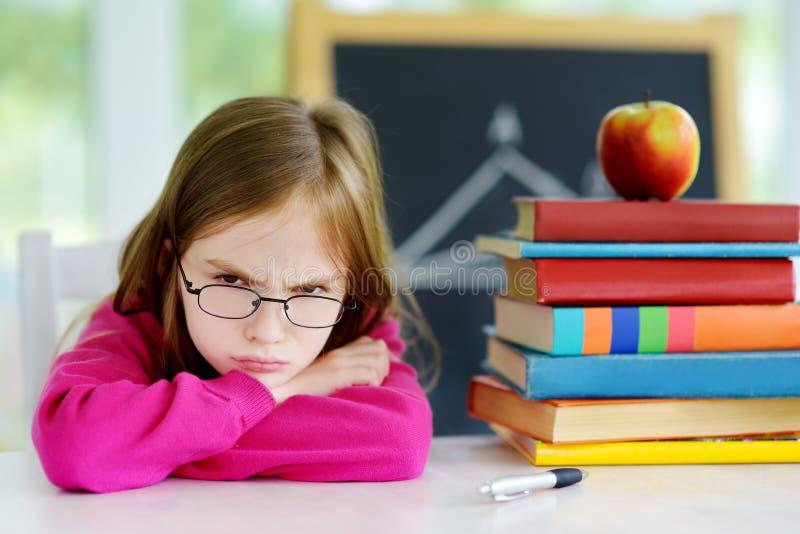 学习与堆的恼怒和疲乏的女小学生在她的书桌上的书 免版税图库摄影