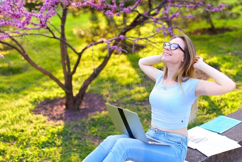 学习与膝上型计算机和纸的俏丽的女孩,放松在公园 免版税库存图片