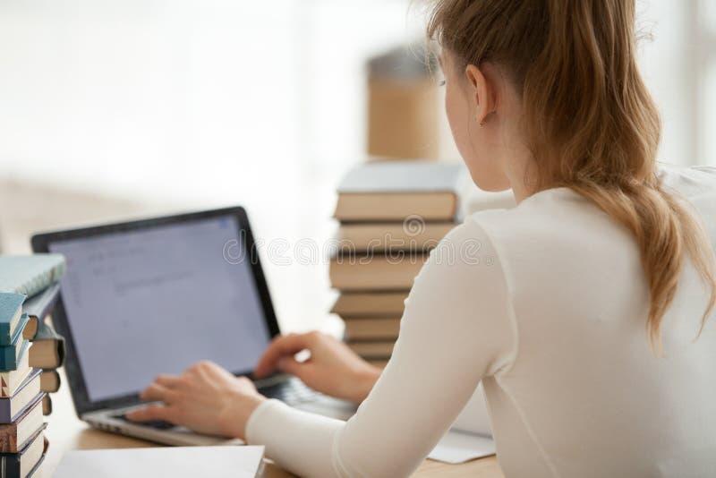 学习使用膝上型计算机的学生女孩坐在书桌 图库摄影
