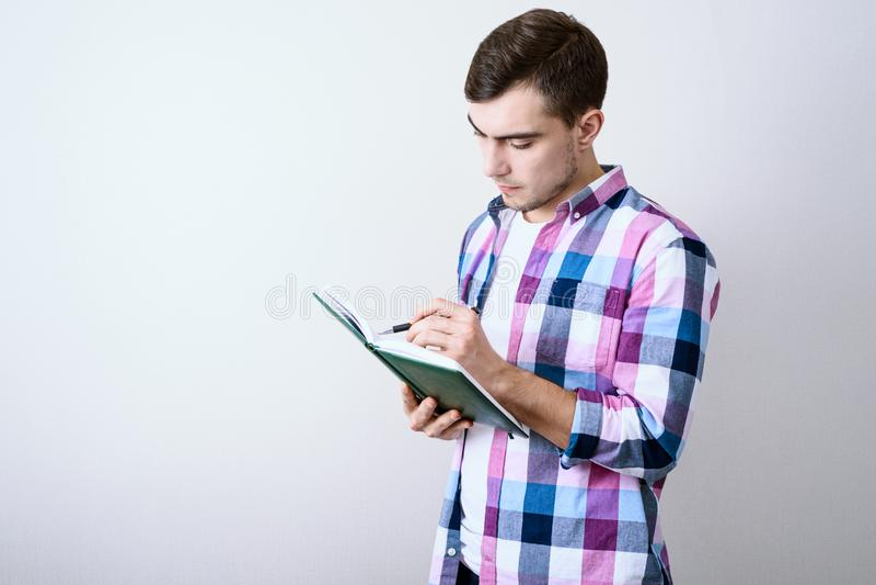 学习关于灰色背景的年轻白男生演讲笔记与拷贝空间 库存照片