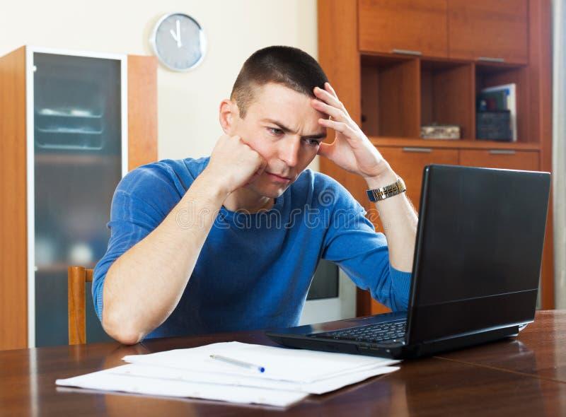 学习关于膝上型计算机的沮丧的人财政信息 库存图片