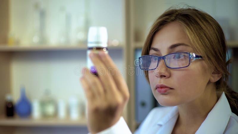 学习医学成份的女性医生,凝视药片容器标签  库存照片