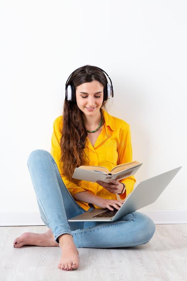 学习和听耳机的妇女 库存图片