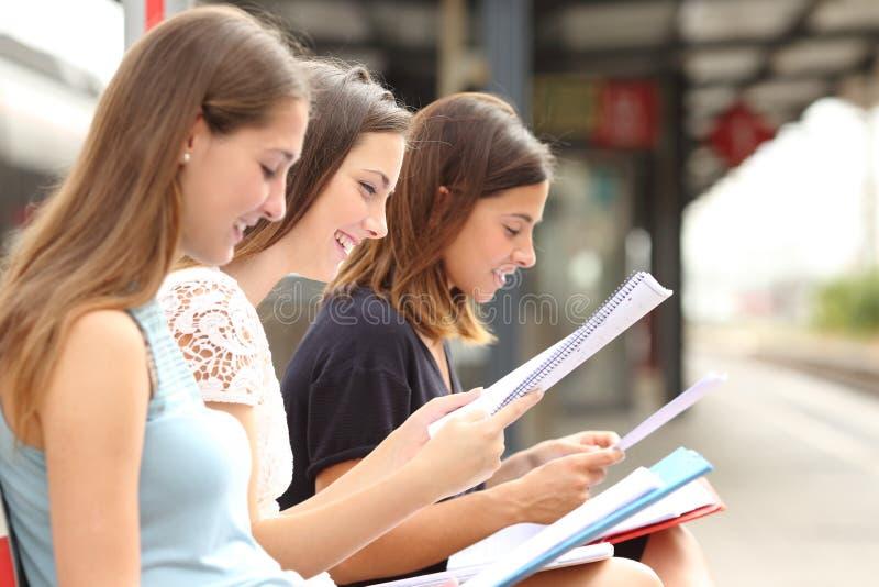 学习和学会在火车站的三名学生 免版税图库摄影