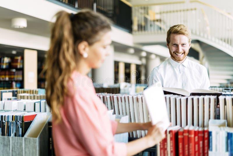 学习和挥动在图书馆里的美丽的愉快的学生 免版税库存照片