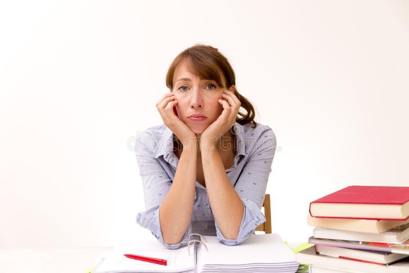 学习和读在图书馆里的少妇,但是有了解材料的困难时期 免版税图库摄影