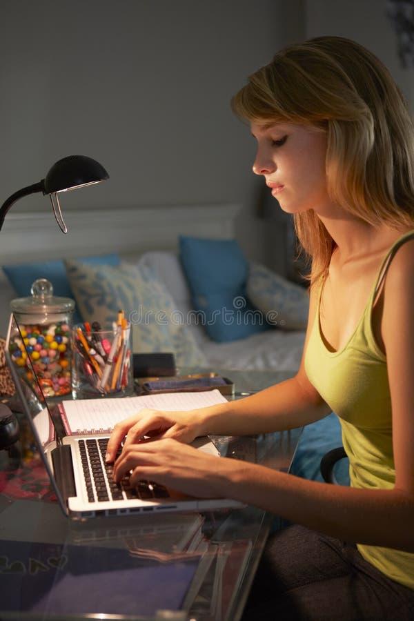 学习在书桌的十几岁的女孩在卧室在膝上型计算机的晚上 免版税库存照片