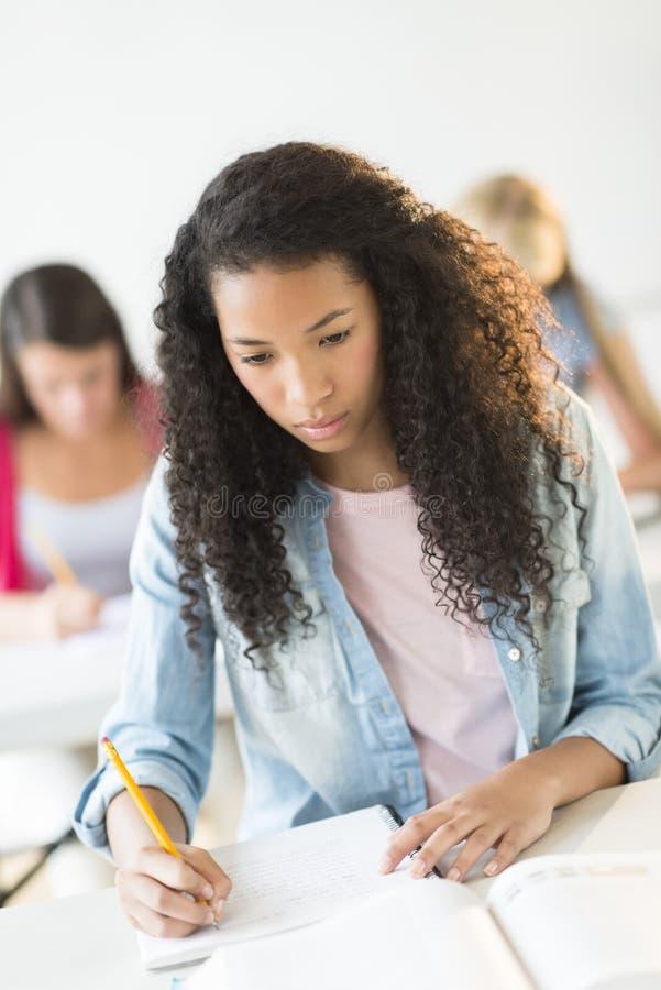 学习在书桌的少年学生在教室 免版税库存图片