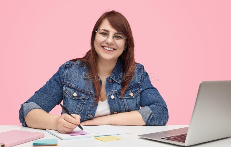 学习在书桌的快乐的肥满少年妇女 库存图片