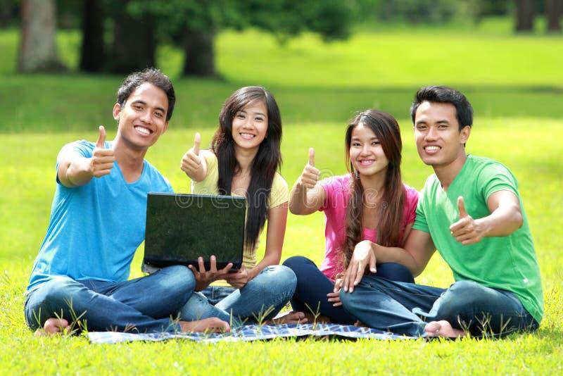 学习在公园的学生使用便携式计算机 库存图片