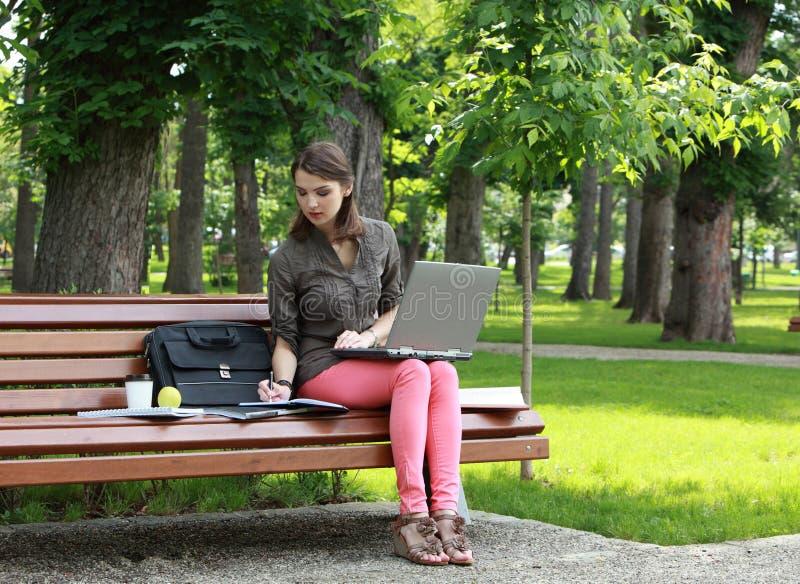 学习在公园的少妇 免版税图库摄影