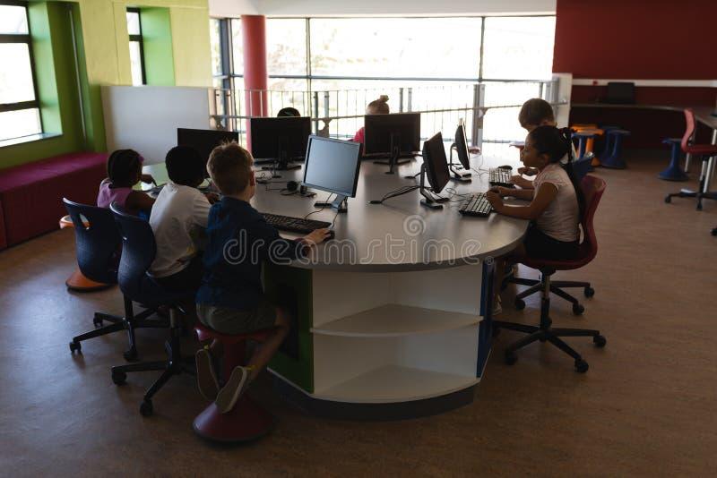 学习在台式计算机的小组schoolkids在学校 免版税库存图片