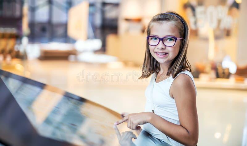 学习在商城的美丽的逗人喜爱的小女孩取向计划 购物中心商店指南 现代触摸屏技术 库存图片