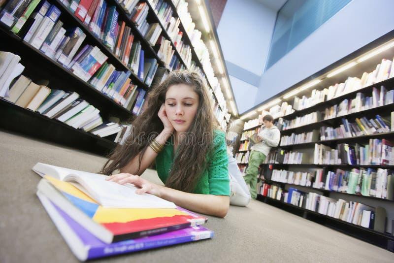 学习在图书馆地板上的学生 免版税图库摄影