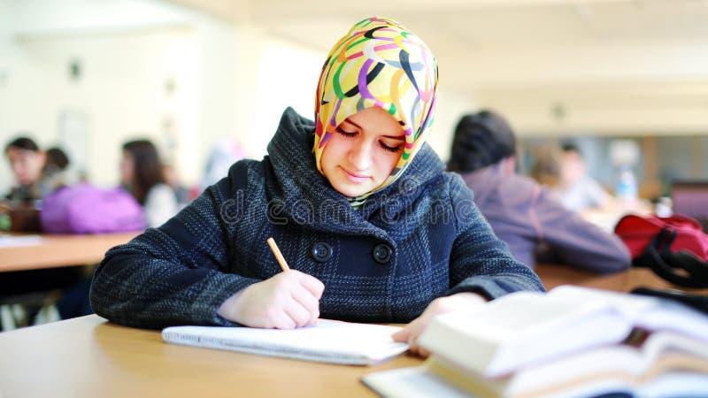 学习在图书馆里的回教女孩 免版税图库摄影