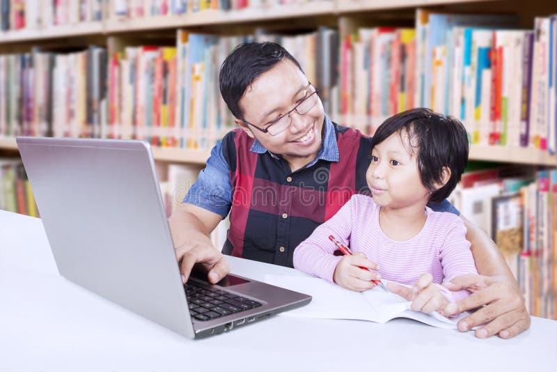 学习在图书馆里的女孩和她的老师 免版税库存照片