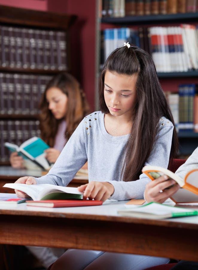 学习在图书馆里的少年女小学生 免版税库存照片