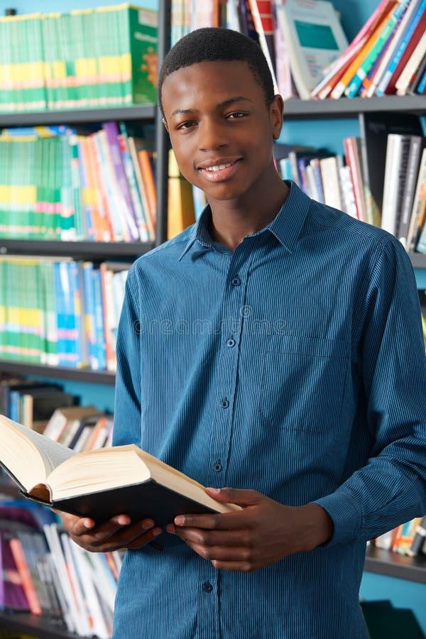 学习在图书馆里的男性少年学生 免版税库存照片