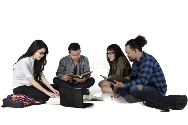学习在地板上的多种族学生 库存照片