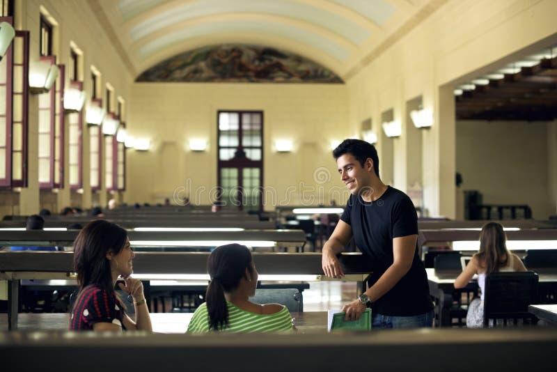 学习在学校图书馆里的小组愉快的学生和朋友 免版税库存图片
