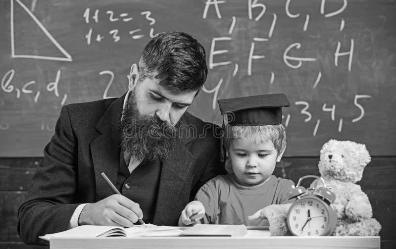 学习在学校的繁忙的孩子 老师,检查家庭作业的父亲,帮助给男孩,儿子 礼服的老师和学生 库存图片