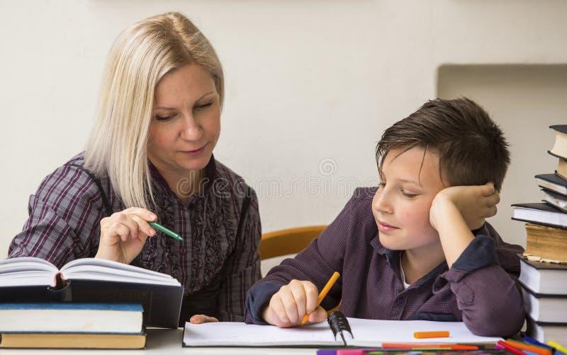 学习在家庭教师帮助下的男小学生 教育 图库摄影
