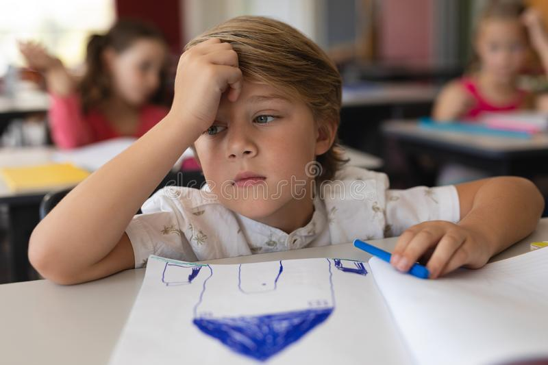 学习在教室的哀伤的男小学生坐在书桌在学校 图库摄影