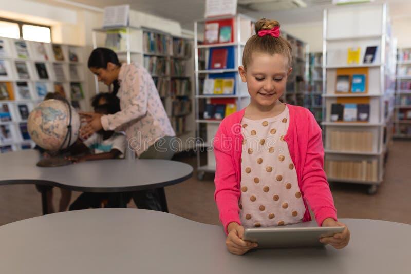 学习在数字片剂的女小学生在桌上在学校图书馆中 库存照片