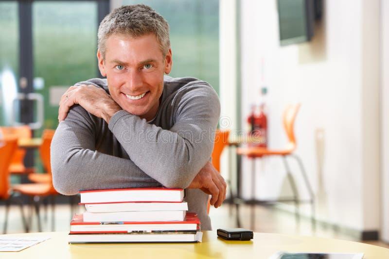 学习在有书的教室的男性成熟学生 图库摄影
