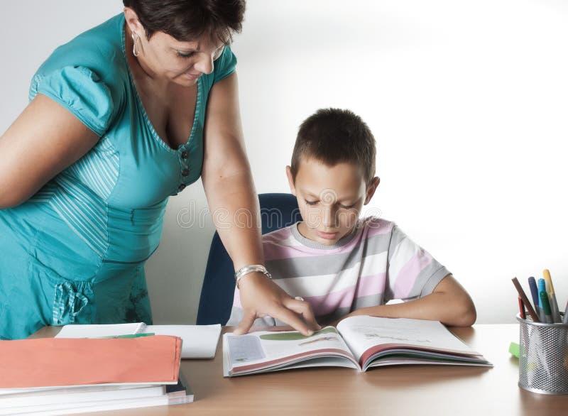学习在有教师的教室的男小学生 免版税图库摄影