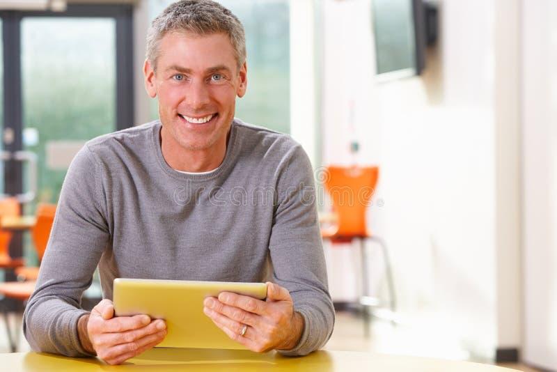 学习在有数字式片剂的教室的成熟学生 免版税库存照片