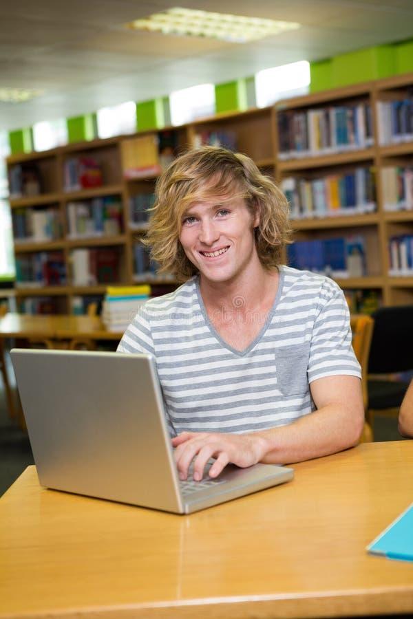 学习在有膝上型计算机的图书馆里的学生 库存照片