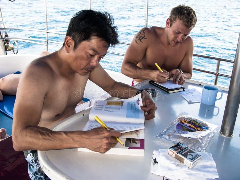 学习在机上下潜小船的佩戴水肺的潜水学生 库存图片