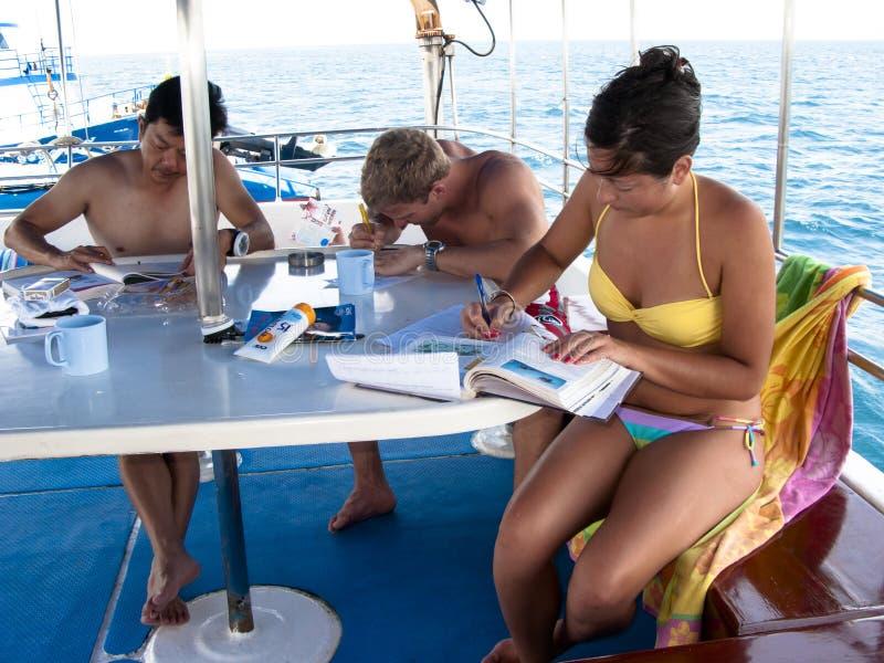 学习在机上下潜小船的佩戴水肺的潜水学生 免版税库存照片