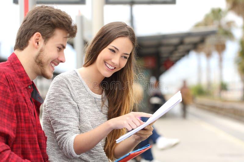 学习在火车站的学生夫妇  库存图片